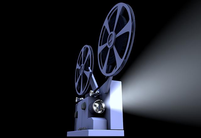Projektor filmowy na ciemnym tle, emitujący wiązkę światła.