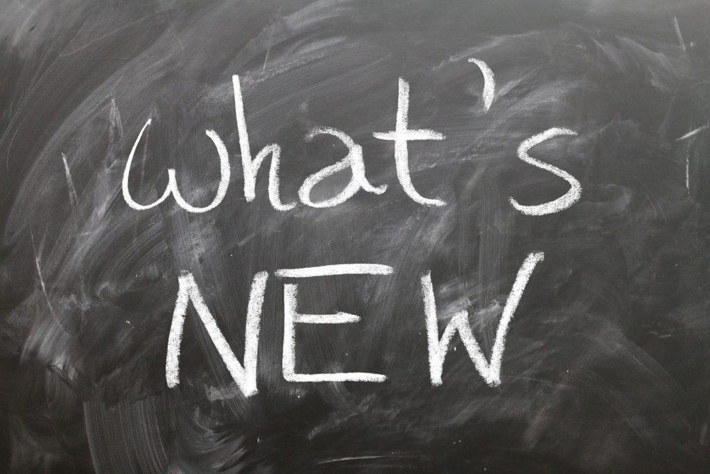 """Na ciemnym tle biały napis """"what's new""""."""