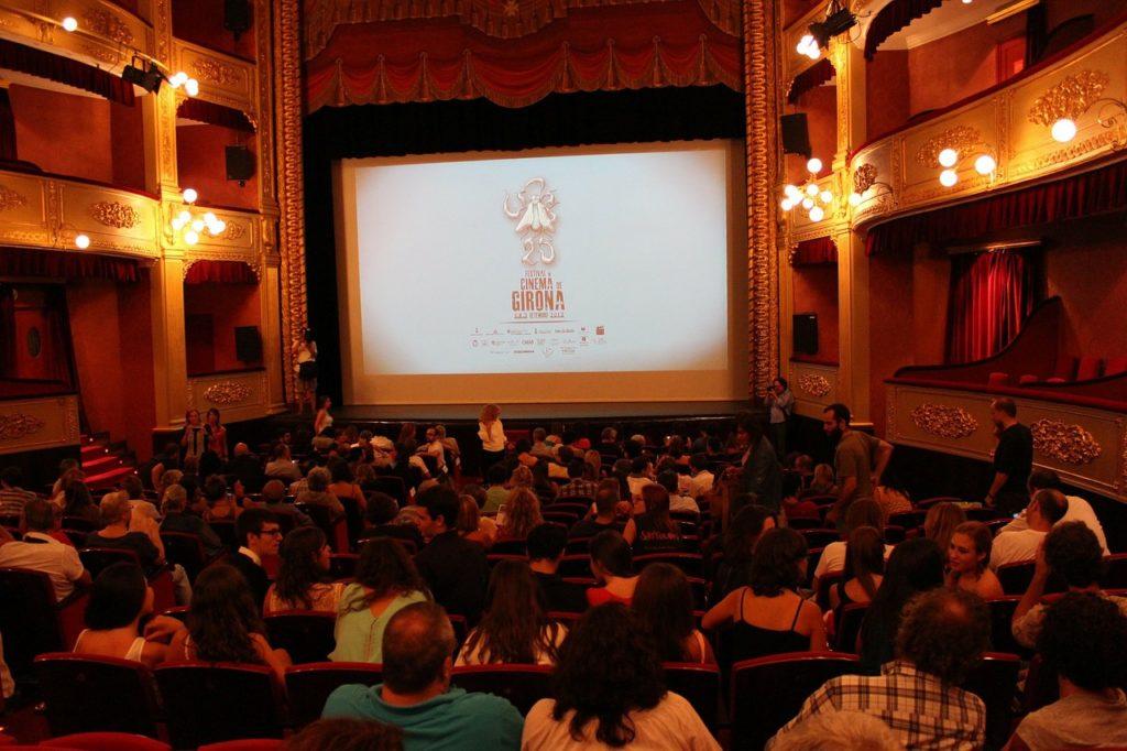 Sala kinowa, publiczność ogląda wyświetlany obraz na dużym ekranie.