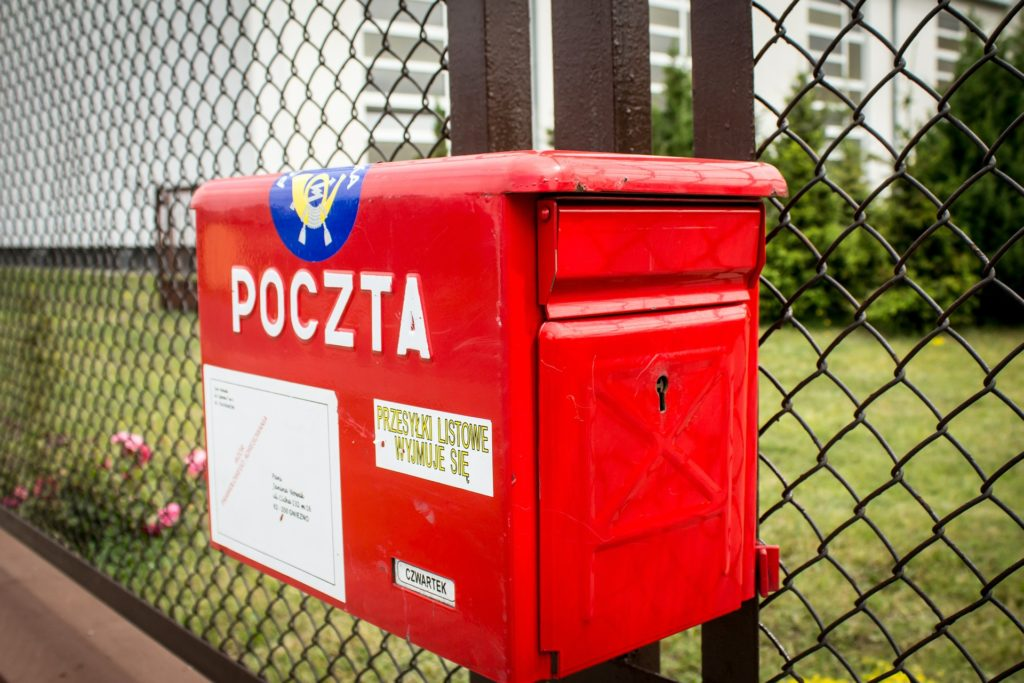 Na tle ogrodzenia czerwona skrzynka pocztowa.