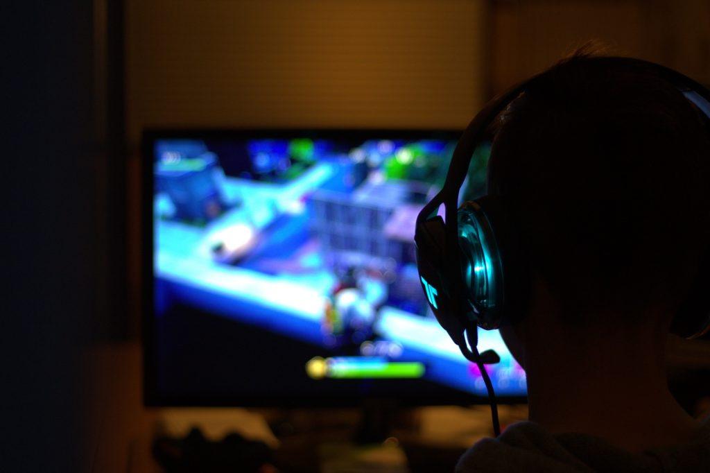 Mężczyzna z słuchawkami skierowany w stronę włączonego monitora komputerowego.