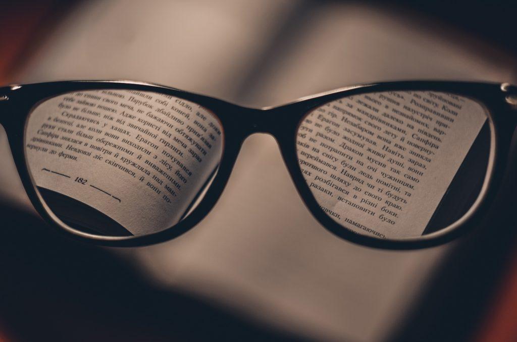 Na tle ksiązki okulary powiększające tekst.