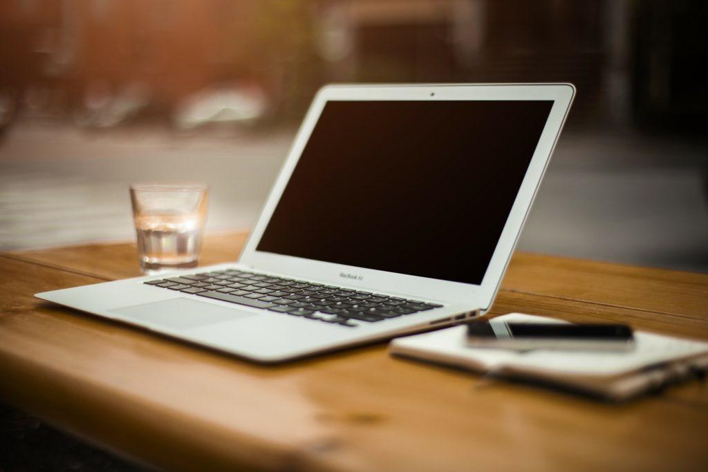Biały laptop na stole, obok niego po lewej stronie jest szklanka, a po prawej zeszyt.
