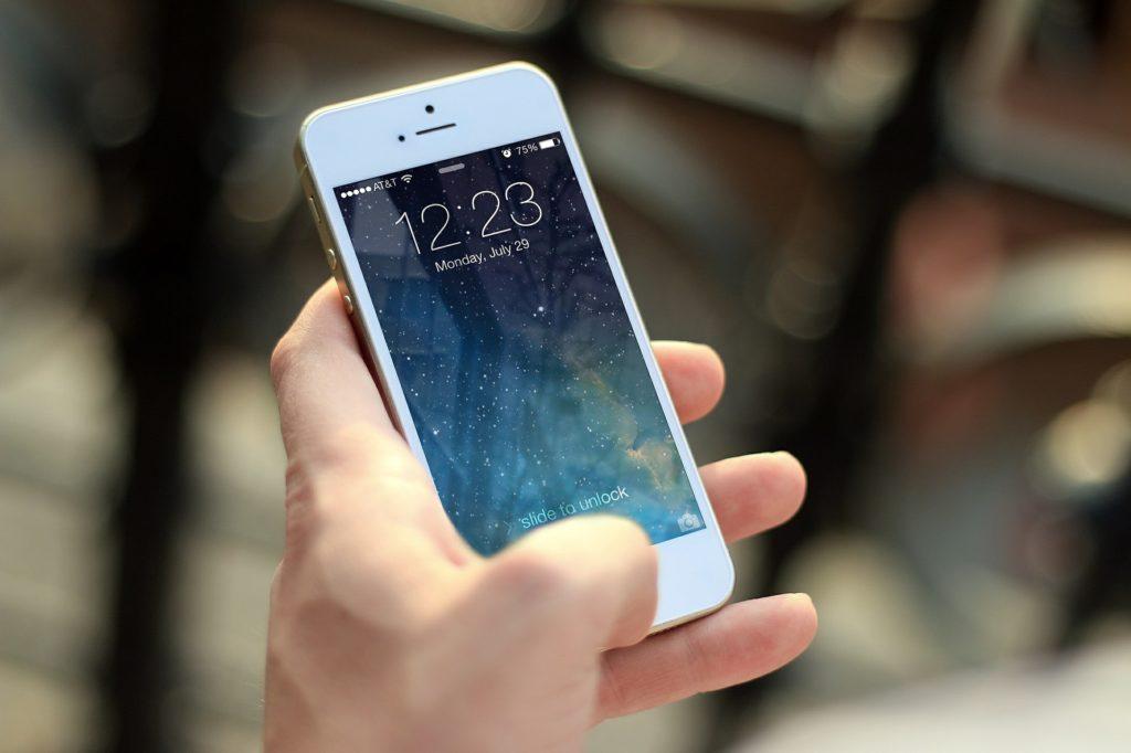 Na jasnym tle smartphone w dłoni.