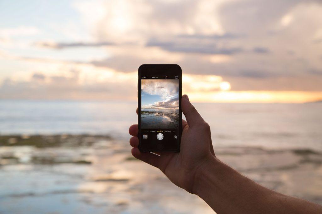 Na tle morza, smartfon w dłoni.