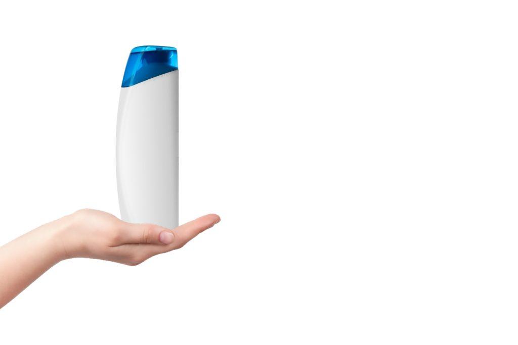 Na jasnym tle dłoń, na której znajduje się plastikowa butelka szamponu bez nazwy.