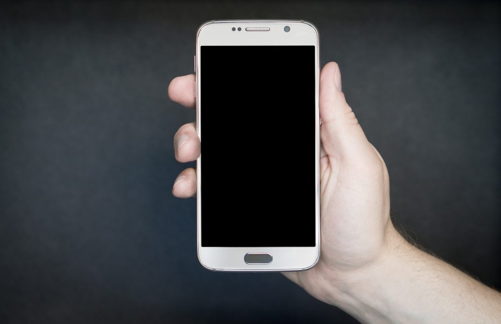 Na ciemnym tle smartfon trzymany w dłoni.