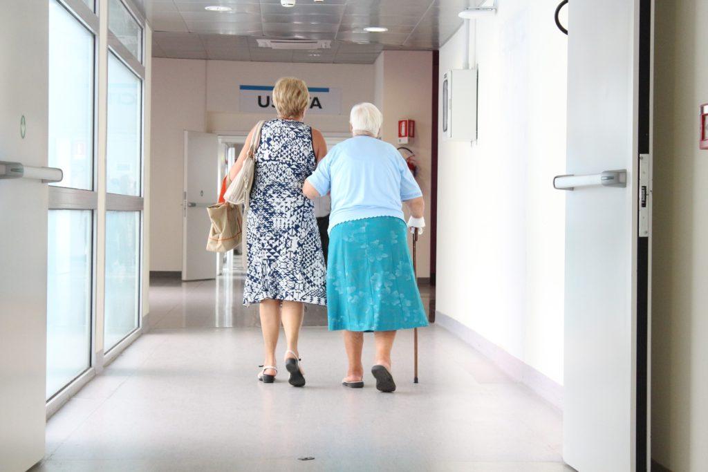 Dwie kobiety idą korytarzem. Jedna z kobiet trzyma pod rękę drugą, jednocześnie korzysta z pomocy laski.