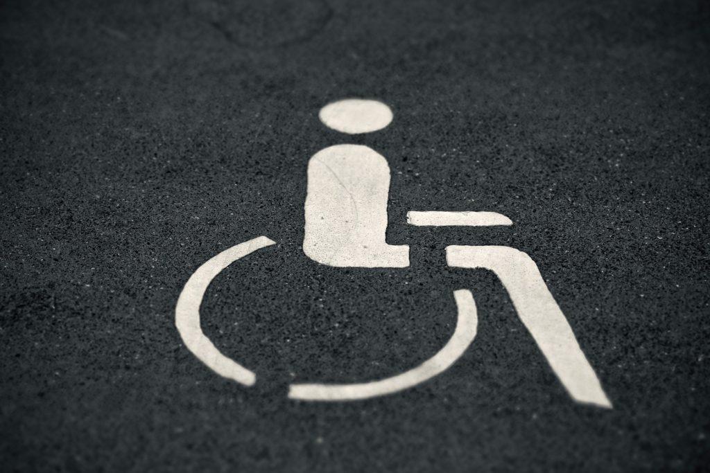 Na ciemnym tle oznakowanie miejsca postojowego dla osoby z niepełnosprawnością.