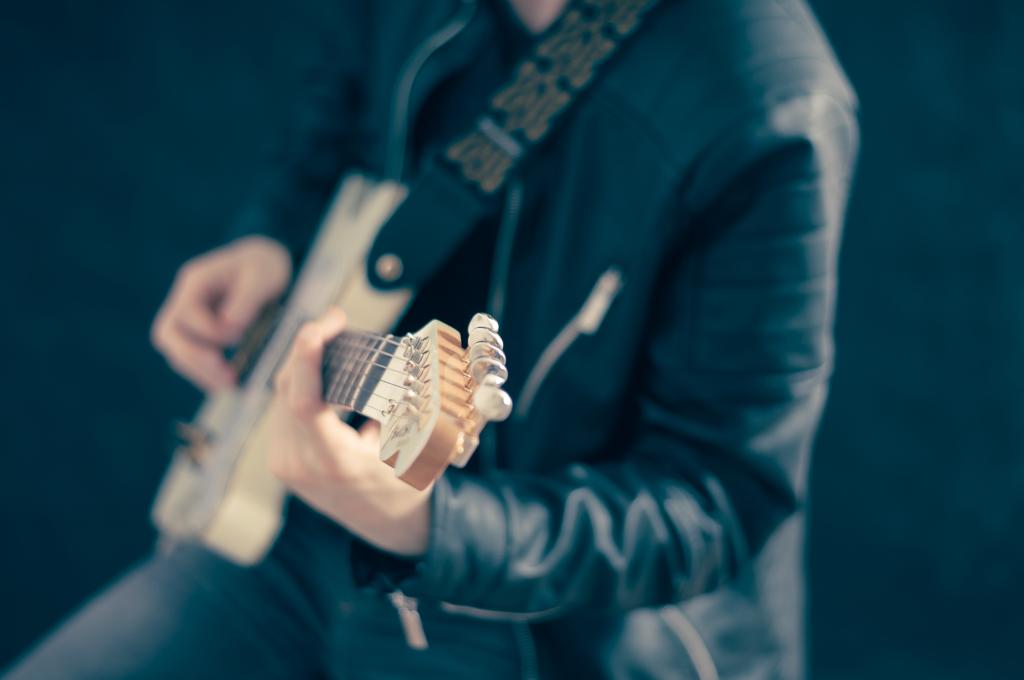 Na ciemnym tle mężczyzna grający na gitarze.
