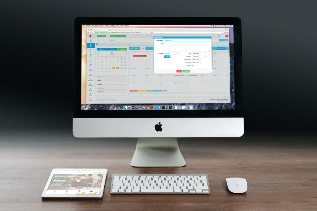 Na ciemmnym tle biały monitor, tablet, klawiatura oraz myszka komputerowa.