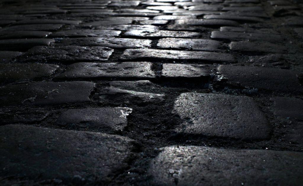 Na zdjęciu fragment brukowanego chodnika z dziurami.