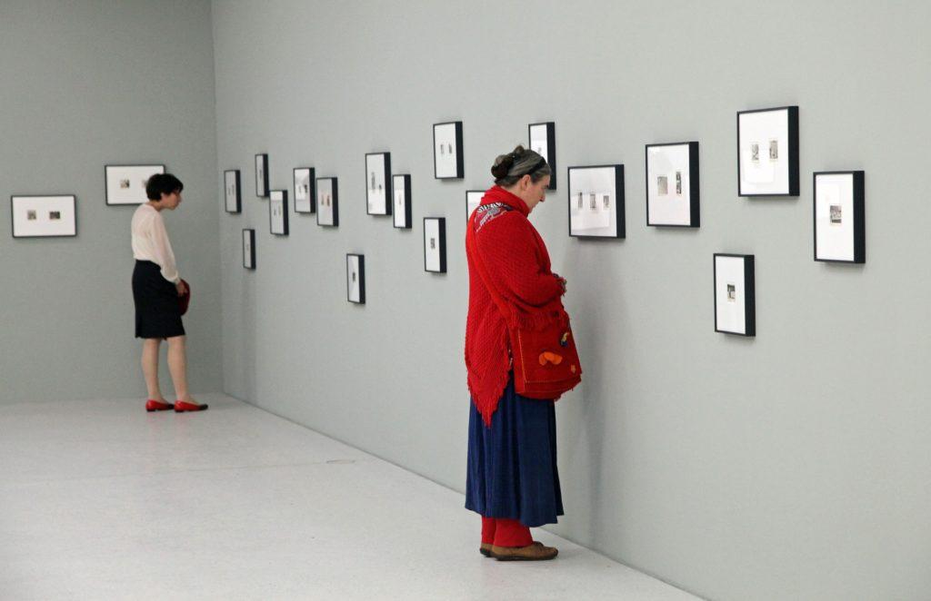 W pomieszczeniu dwie kobiety oglądają obrazki na ścianie.