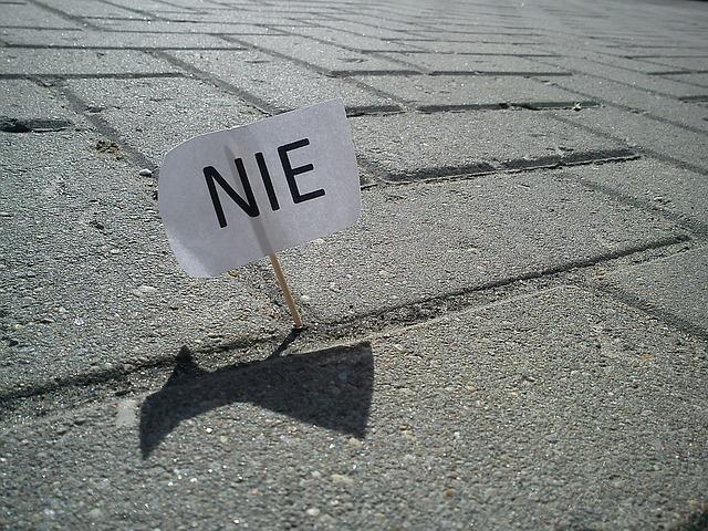 """Grafika ozdobna - chorągiewka z napisem """"Nie"""" wbita w bruk"""
