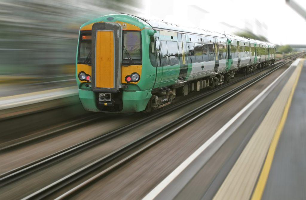 Na szarym tle zielono-pomarańczoy pociąg.