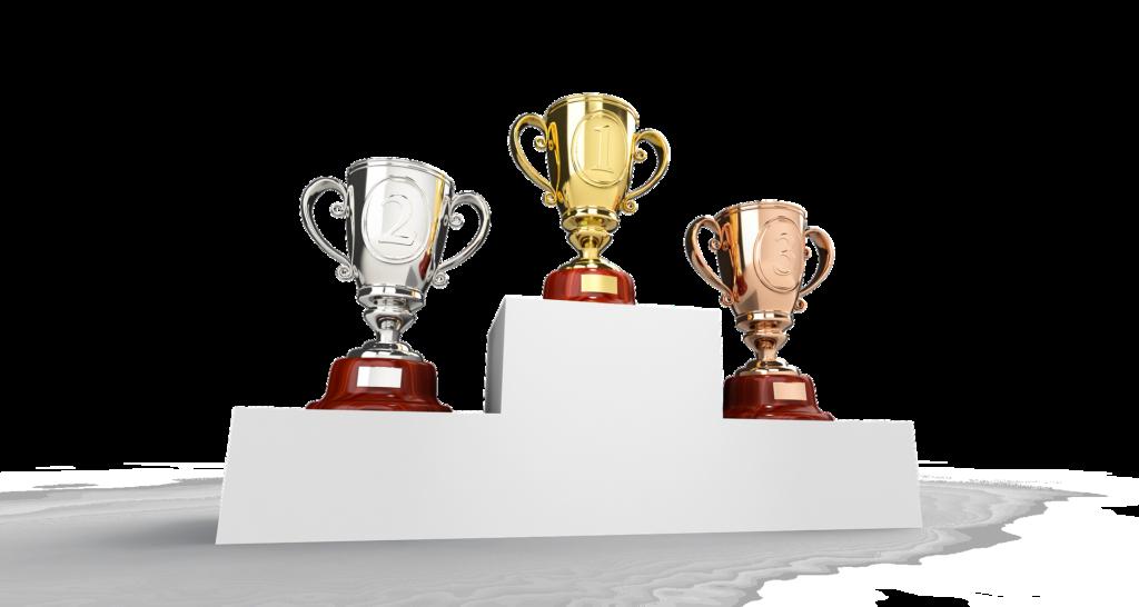 Na jasym tle, na podioum trzy puchary symbolizujące 3 pierwsze miejsca.
