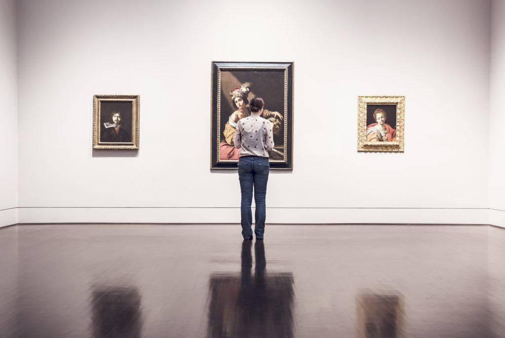 Na jasnej ścianie znajdują sie trzy obrazy, przed nimi stoi kobieta.