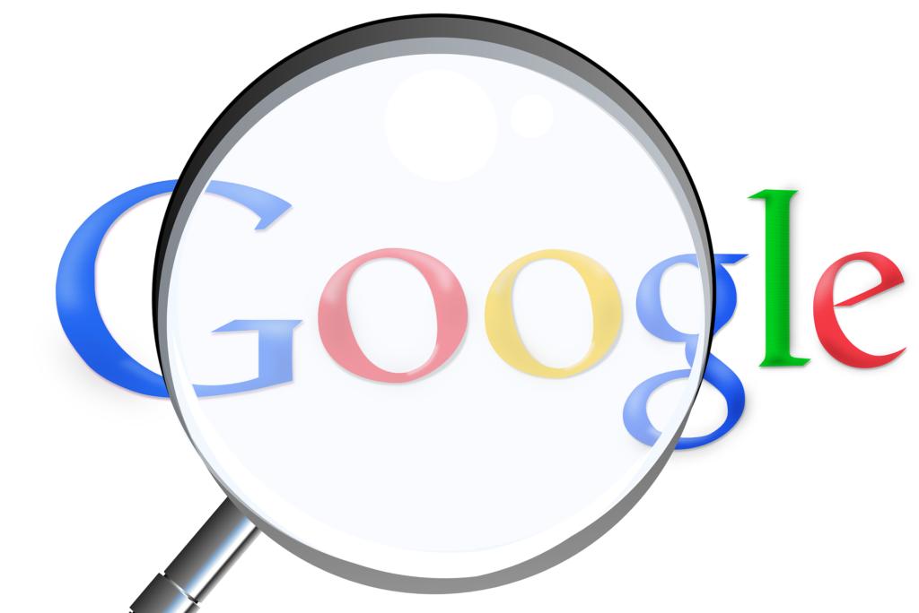Na jasnym tle lupa powiększająca napis google.