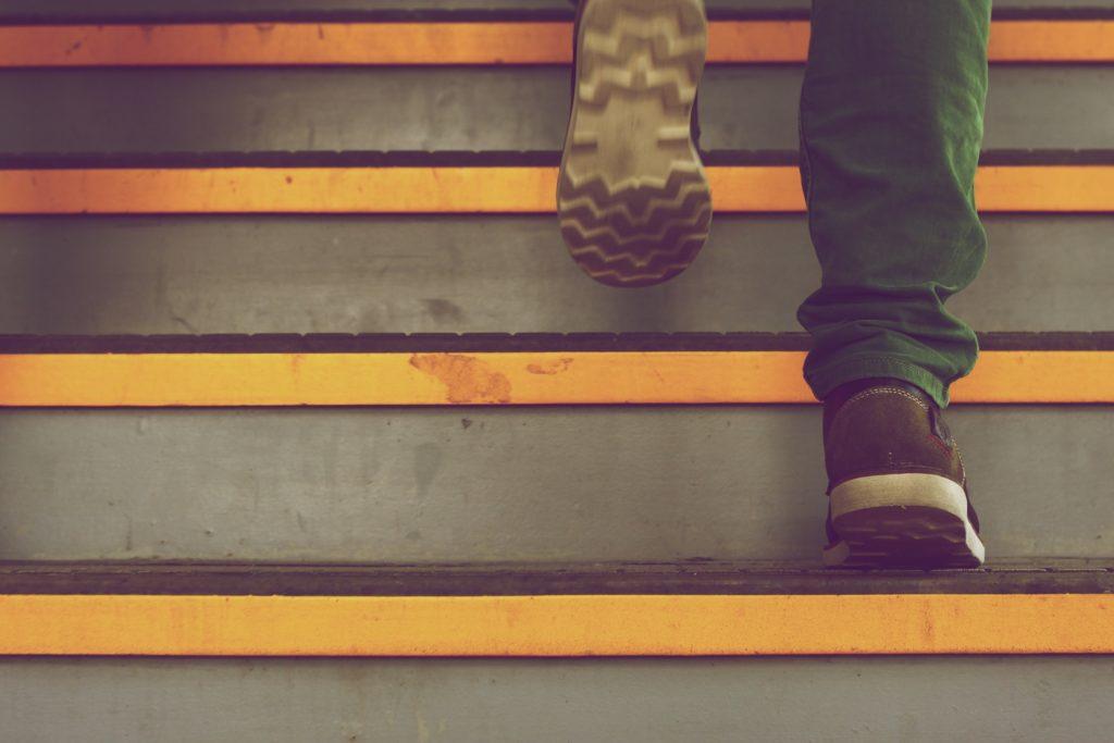 Na zdjęciu schody oraz buty osoby wchodzącej.