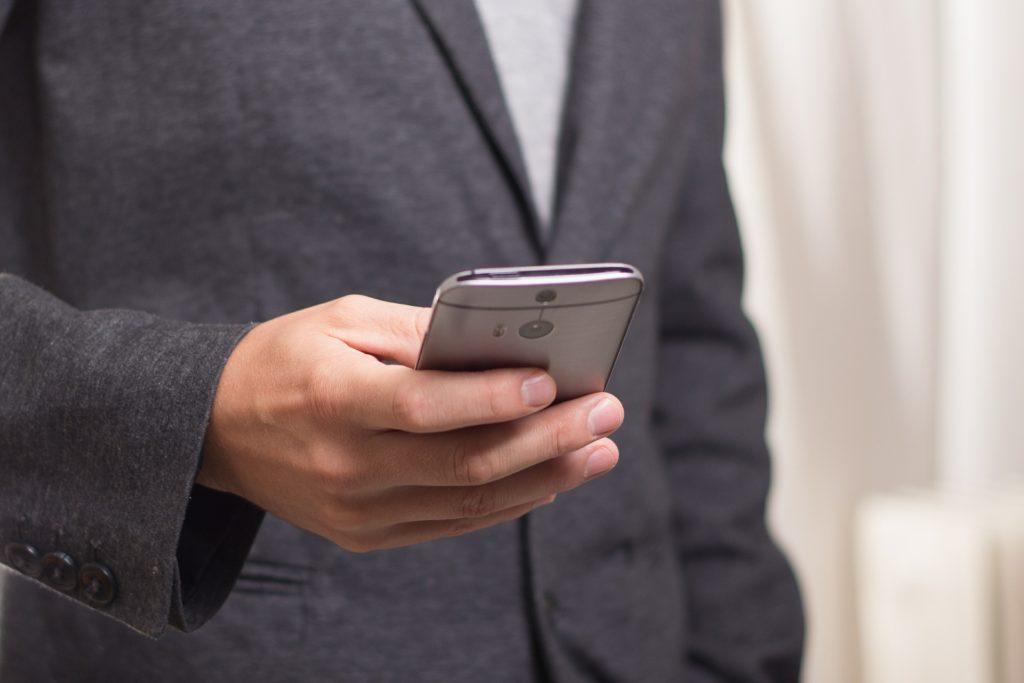 Mężczyzna w ciemnym garniturze trzymający telefon w dłoni.