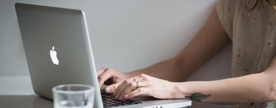 fragment kobiecej sylwetki przy biurku piszącej na laptopie