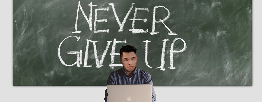 """Nauczyciel przy biurku, przed sobą ma komputer, za nim szkolna tablica z napisem """"NEVER GIVE UP"""""""