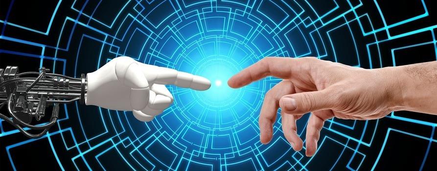 Na zdjęciu widzimy dwie dłonie, jedna człowieka, druga dłoń robota. Obie wskazują na siebie palcem wskazującym.