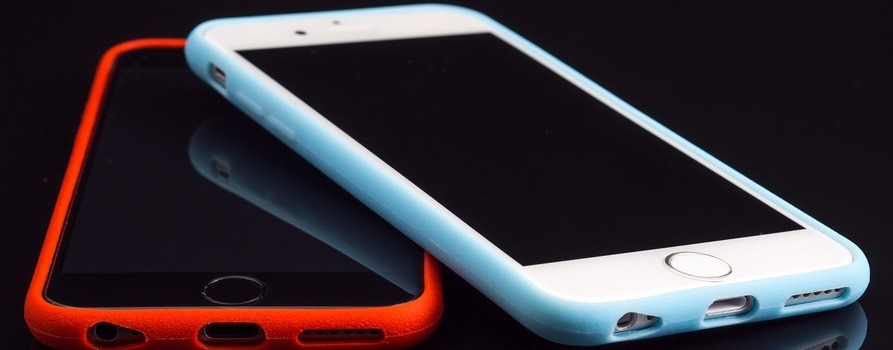 Dwa telefony komórkowe, jeden w czerwonym etui drugi w białym