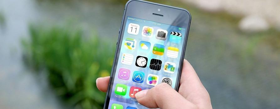 Telefon komórkowy trzymany w dłoni, wyświetlony ekran główny w iPhone