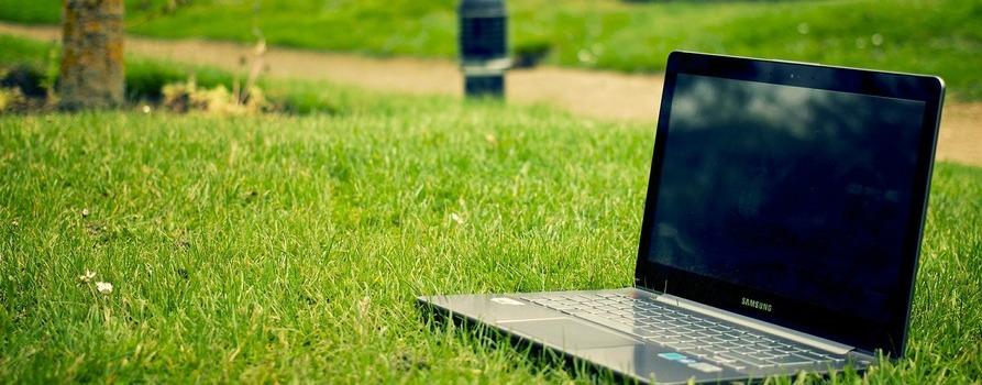 Otwarty laptop leżący na trawniku w parku