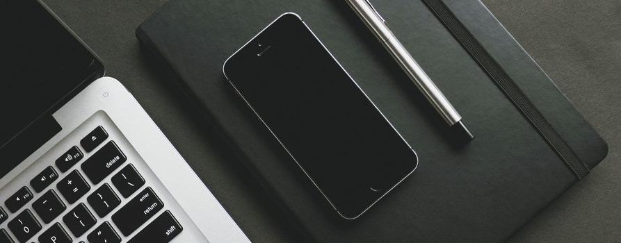 Na zdjęciu widzimy fragment klawiatury laptopa, obok czarny skórzany notes a na nim położonony jest telefon i długopis