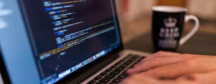 Na zdjęciu widzimy ekran laptopa, na którym wyświetlony jest kod programistyczny, obok stoi kubek