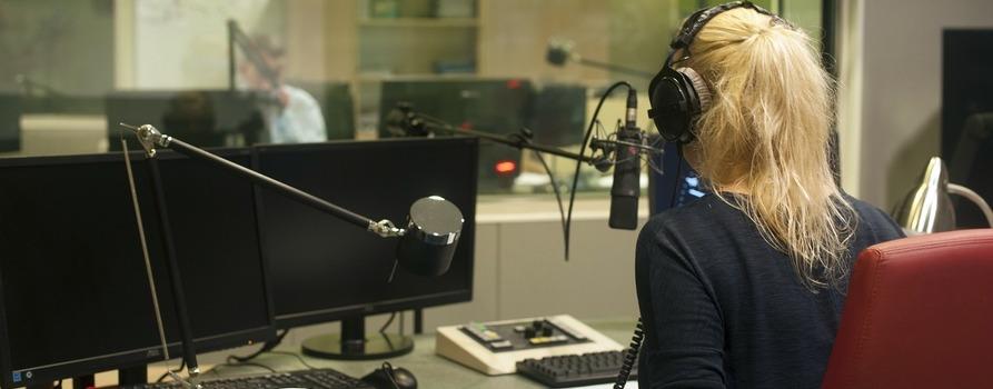 Kobieta siedząca przy konsoli radiowej, ma nałożone duże słuchawki, przed sobą 2 mikrofony radiowe i dwa monitory komputera