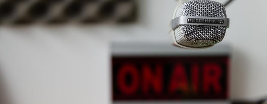 """Na zdjęciu mikrofon radiowy, w tle widać czerwony napis """"ON AIR"""""""