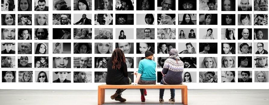 Trzy osoby siedzące na ławce, przed sobą mają ścianę z biało-czarnymi fotografiami