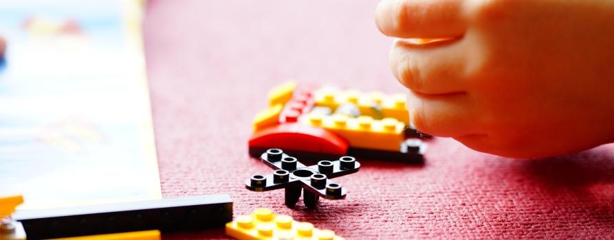 Klocki lego rozłożone na stole, po prawej stronie rączka bawiącego się dziecka