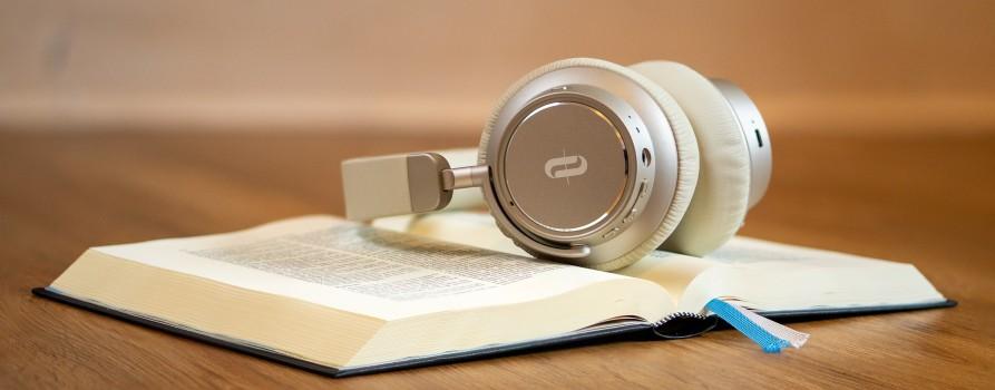 Zdjęcie przedstawia otwartą książkę i słuchawki położone na niej