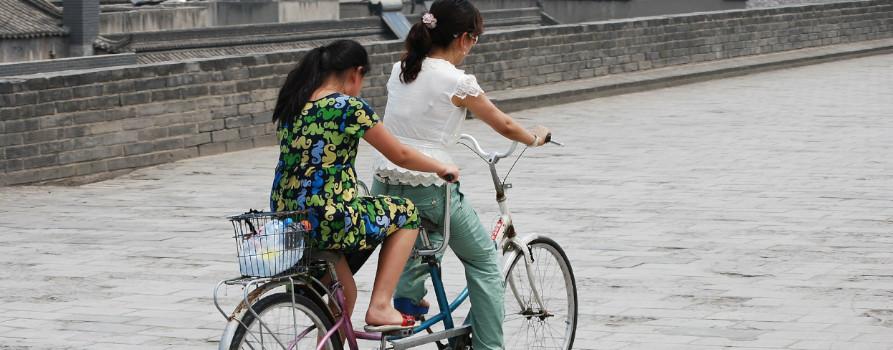Dwie kobiety jadące na tandemie rowerowym.