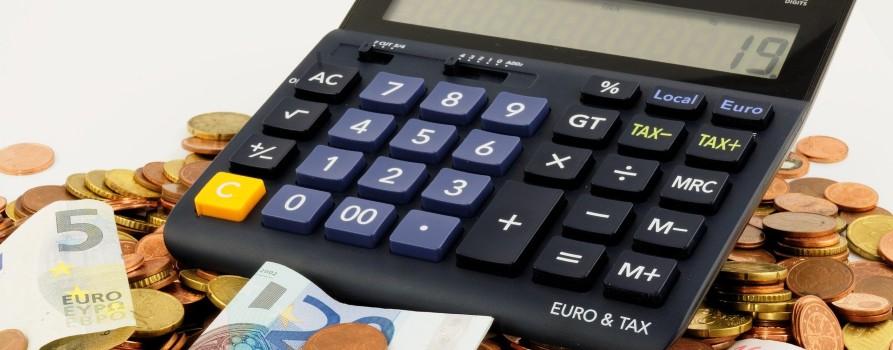 Stos monet i banknotów euro. Na jego szczycie leży kalkulator.