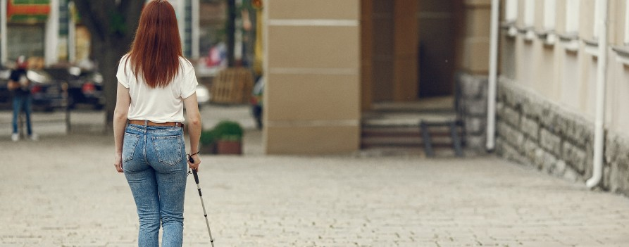 Kobieta spacerująca po mieście z białą laską.