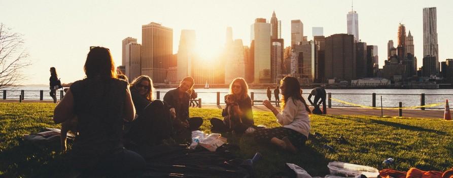 Grupa młodych ludzi siedząca na trawie nad brzegiem rzeki, za nimi widać zabudowania miasta.