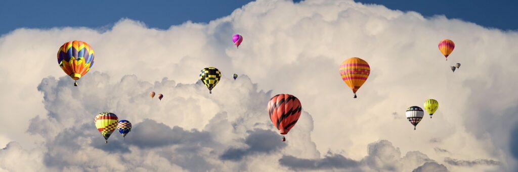 Kilkanaście kolorowych balonów na tle białej kontrastowej chmury. Zdjęcie wykonane podczas zlotu balonów.