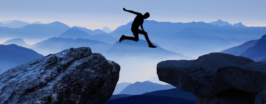 Sylwetka mężczyzny skaczącego między dwoma skałami, które oddziela przepaść