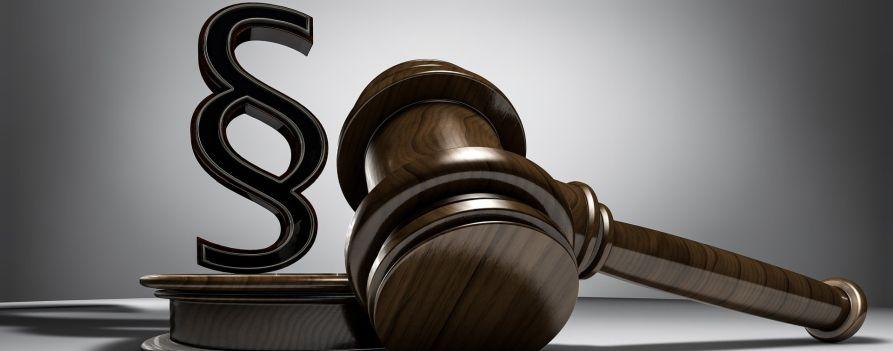 Młotek używany w trakcie procesu przez sędziego, obok znak paragrafu
