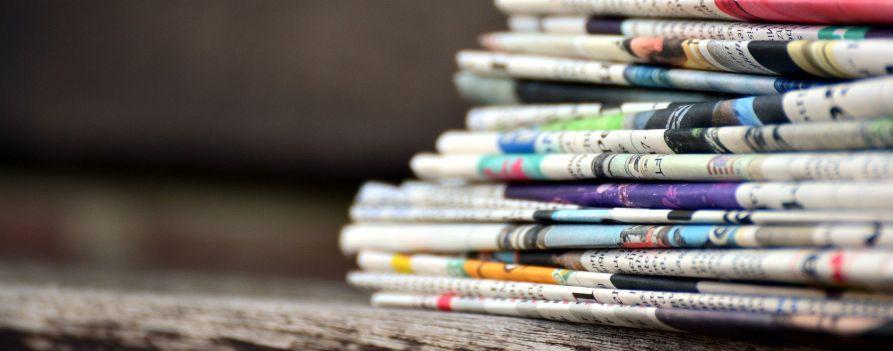 Duży stos gazet ułożonych jedna na drugiej, wyraźnie widoczne kolorowe grzbiety złożonych gazet