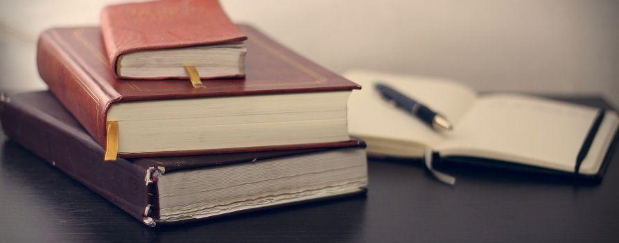 Otwarty kalendarz i trzy notesy na biurku