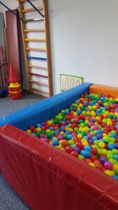 sala gimnastyczna z basenem z kolorowymi piłeczkami