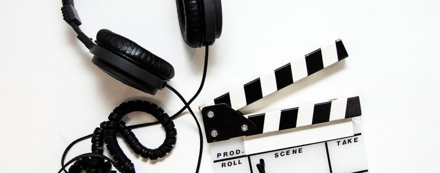Cyfrowy zegar - filmowy klaps, obok niego leżą słuchawki