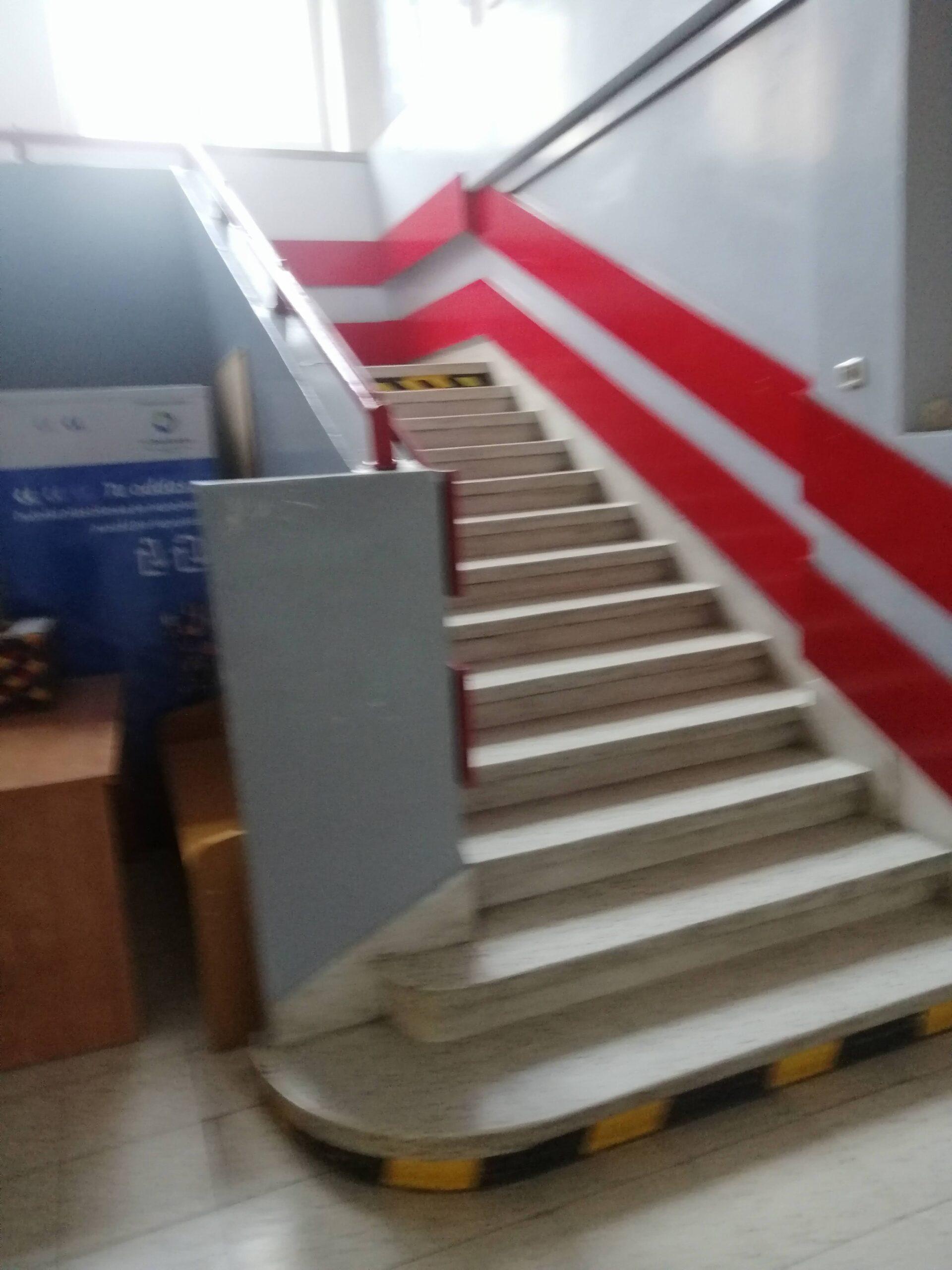 schody wewnątrz budynku z czerwoną poręczą