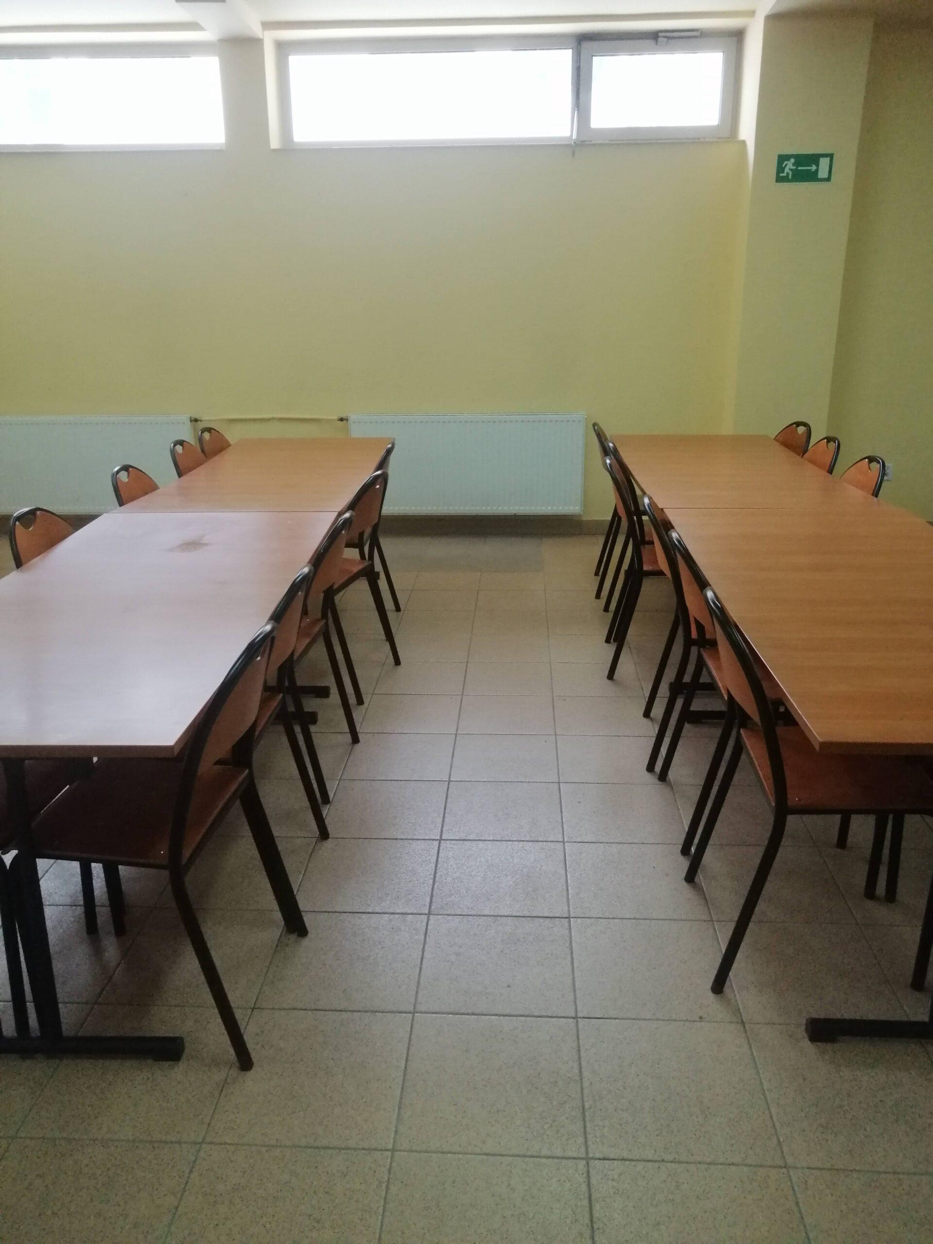 wnętrze klasy. w dwóch rzędach ustawione ławki szkolne z krzesłami